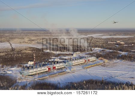 Plant of oil and gas processing industry in winter aerial view. Helicopter flying over the plant buildings.