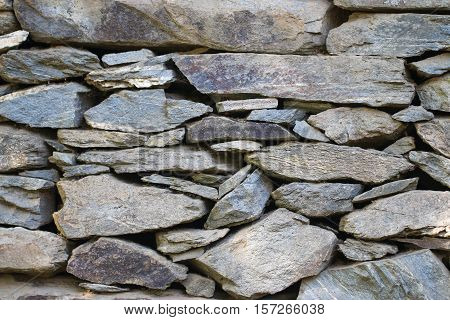 Stone wall built from stones and rocks of different sizes in black and white.