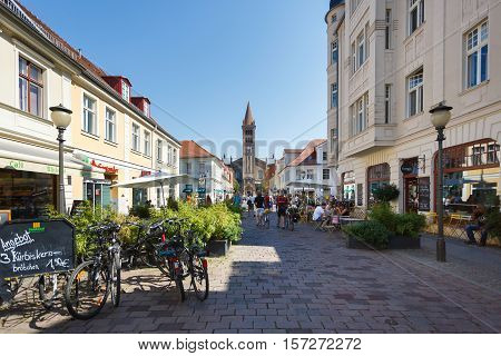 Potsdam Germany August 27 2016: Tourists are walking in a street on the background of the Saint Peter and Paul Church
