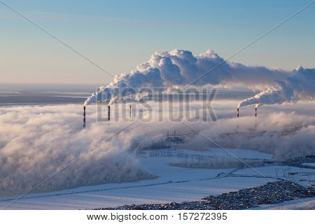 Power station with rising steam from pond to sky in winter season aerial view.