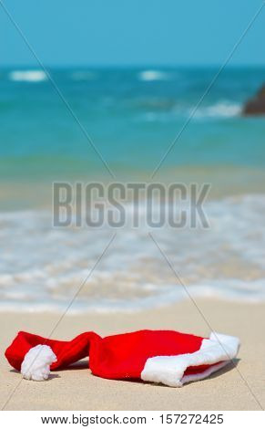 Red Santa Claus's hat on a beach.