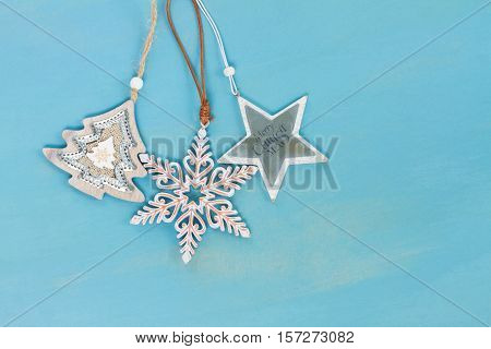 Blue and white christmas with stars hanging on blue wooden background
