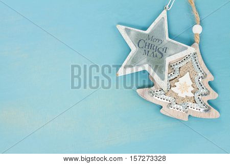 Blue and white christmas with star and christmas tree on blue wooden background