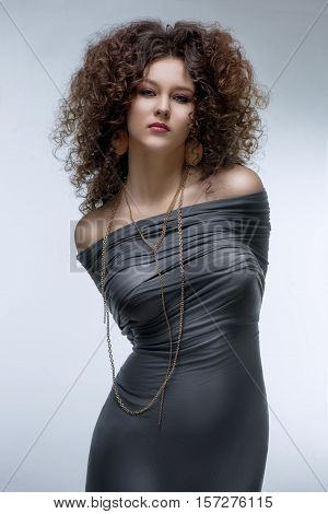 Brunette girl with a curly hairstyle and carnivore look with her hands tied