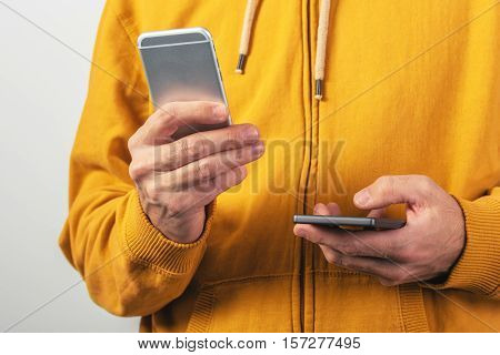 Man using two mobile phones for SMS communication male person wearing yellow shirt with zipper sending text messages from dual smartphone devices