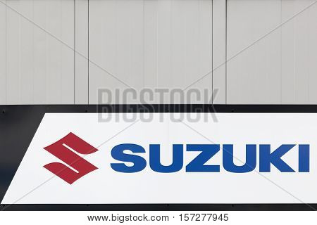 Macon, France - October 10, 2016: Suzuki logo on a wall. Suzuki is a Japanese multinational corporation which specializes in manufacturing automobiles, four-wheel drive vehicles and motorcycles