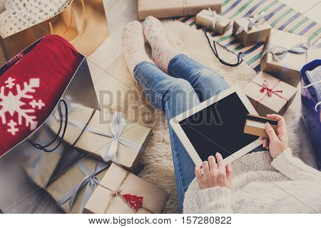 Christmas online shopping top view. Female buyer click at screen of tablet, make internet order with credit card. Woman buy presents for xmas eve, among gift boxes and packages. Winter holidays sales