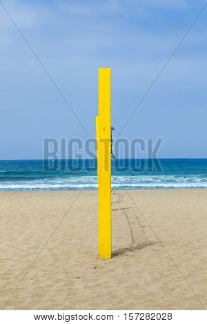 yellow volleyball post at the beach in blue