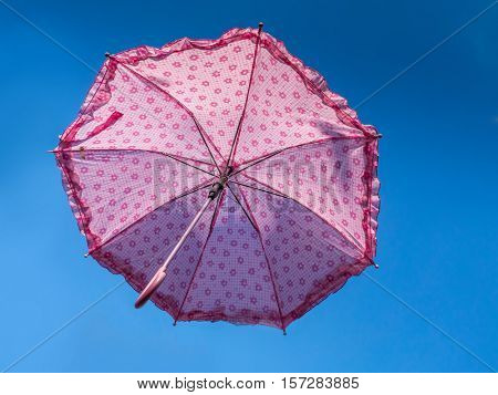 Pink umbrella rising high into the blue sky