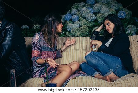 Young woman talking with female friend sitting on sofa in a outdoors party. Friendship and celebrations concept.