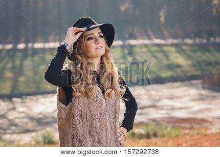 Winter portrait of a blonde hippie young woman wearing a hat