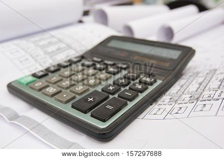 Part of architectural project showing calculator and blueprints
