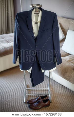 Suit, shirt, trousers, shoes of groom hanging on hanger, wedding clothing