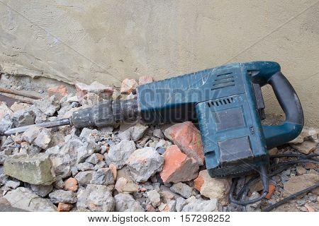 broken Hammer drill lying on a rock outdoors