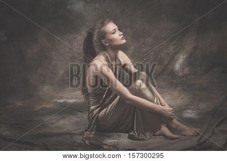 barefoot elegant young woman in golden dress sit full body shot studio