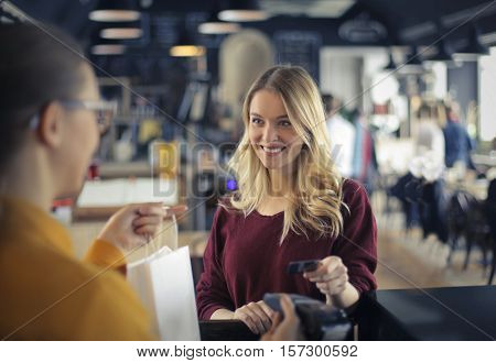 girl at the counter paying by credit card