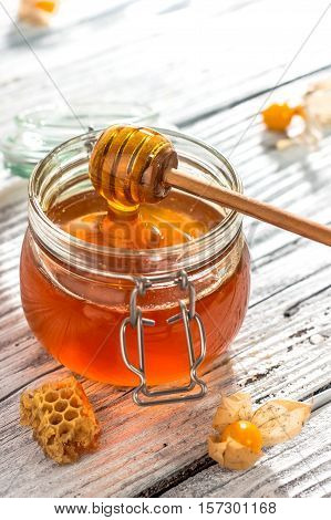 Fresh organic honey on rustic wooden background