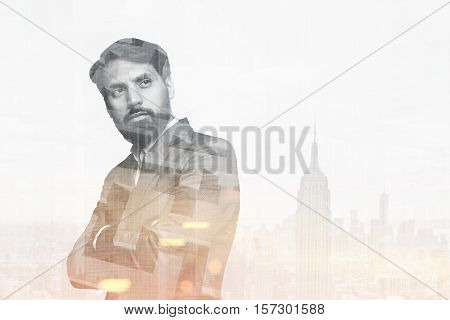 Portrait of a bearded businessman standing with his arms crossed in a city. Toned image. Double exposure