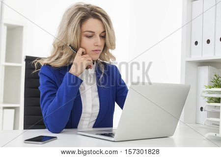 Serious busiensswoman in blue blazer is thinking and reading a document from her laptop screen