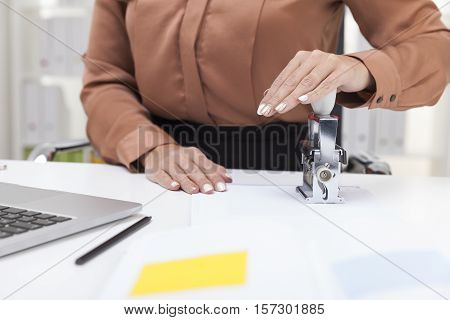 Woman In Brown Blouse Is Using A Stamp
