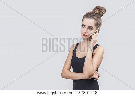 Portrait of a girl with a bun who is having a phone conversation and looking sceptical and not so pleased. Mock up
