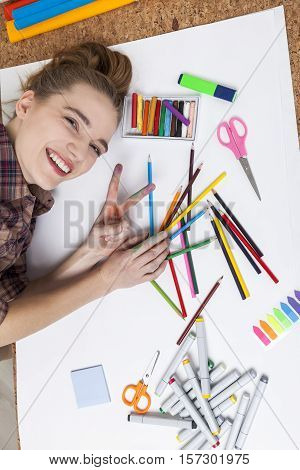 Smiling woman painter is lying on her table near heaps of pencils and markers and smiling to the camera. Concept of a creative person