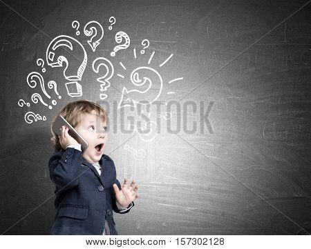 Adorable little boy is standing with his smartphone near a blackboard with question marks and talking. Mock up