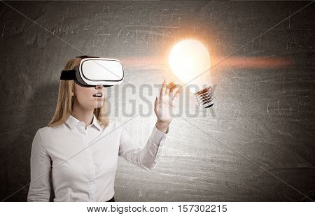Blond woman in virtual reality glasses is standing near a blackboard with a glowing light bulb. Concept of hi tech idea. Toned image