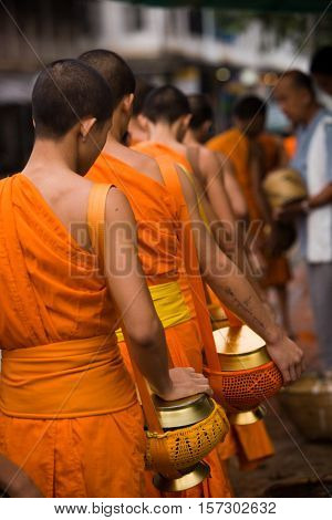 Luang Prabang, Laos - July 25, 2008 : Monk Alms Giving Procession. Every morning the main street of Luang Prabang, Laos is lined with people kneeling and offering alms to the procession of local monks.