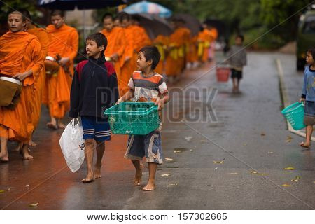Luang Prabang, Laos - July 25, 2008 : Monk Alms Giving Procession.Every morning the main street of Luang Prabang, Laos. Dozens of children begging during the procession of local monks.