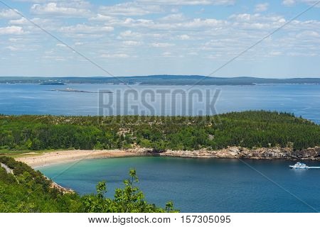 A view of Sand Beach in Acadia National Park Maine. Small bay with tour boat pasing through. People on the beach