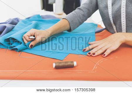 Side veiw of woman's hands drawing a pattern on bright blue material at her workplace in a tailor shop