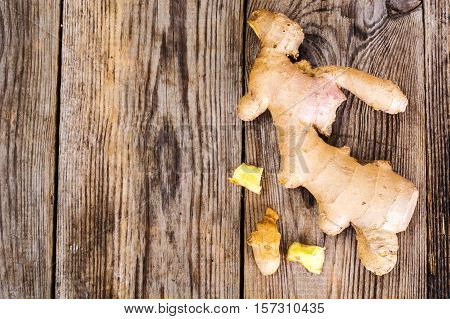 Fleshy fragrant ginger root on wood. Studio Photo