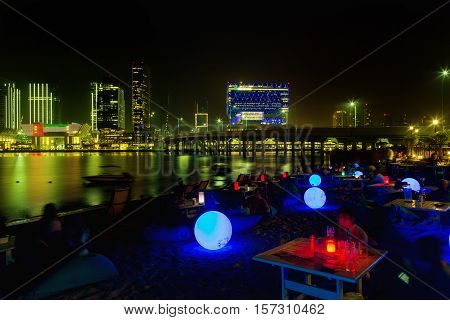 Night party on the beach in Abu Dhabi with a large blue luminous balls. Al Maryah Island skyline at dusk. Abu Dhabi United Arab Emirates Skyscrapers illuminated by the setting sun in gold Abu Dhabi Emirates