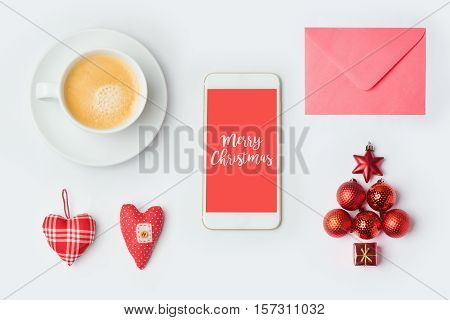 Smartphone with Christmas decorations and coffee cup. Christmas mock up template. View from above. Flat lay