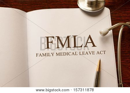 Page with FMLA Family Medical Leave Act on the table with stethoscope medical concept