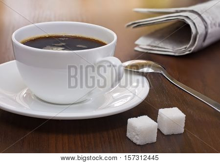 Coffee cup lump sugar (sugar cubes) and newspapers on a table