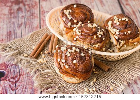 Homemade buns with marzipan and cinnamon in a wicker basket on a napkin of burlap on the old wooden table.