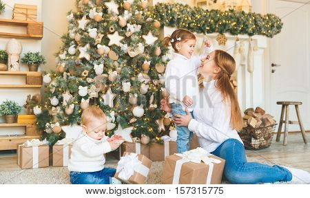 happy family mother and two children on Christmas morning at the Christmas tree with gifts