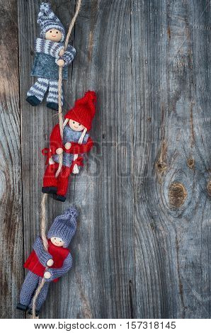 Rag dolls weigh on a rope gray wooden background with empty place