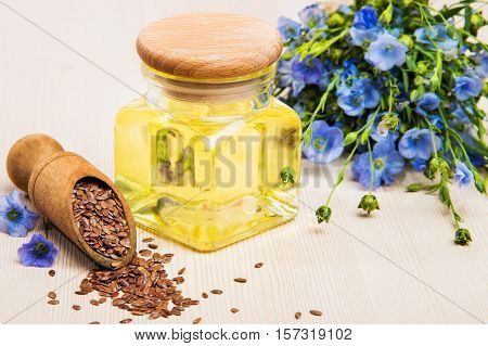 Linseed oil, flax seeds, and flowers on a light background