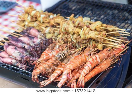 Street food - Side view of grilled sepia prawns and chicken shish kebab on the grill
