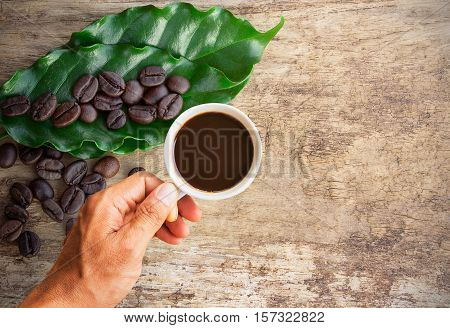 Business man holding a cup of coffee with coffee beans on wooden table background. copy space
