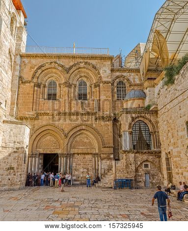 JERUSALEM, ISRAEL - JUNE 19, 2015: Tourists and pilgrims walking at the main entrance of the Church of the Holy Sepulchre in Old City.