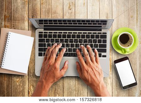 Business man is working by using a laptop computer on vintage wooden table. Hands typing on a keyboard. Top view. Business concept