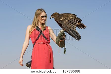 a woman with a greater spotted eagle (clanga clanga) in a desert near Dubai