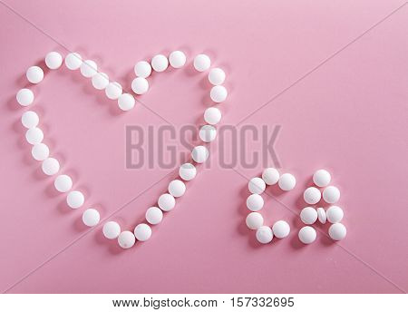 pills forming shape to heart and CA - calcium alphabet on pink background