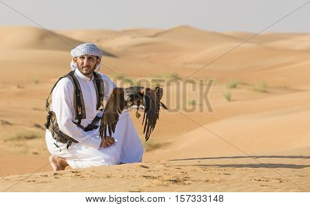 Dubai UAE November 19th 2016: A falconer in traditional outfit training a Harrier Hawk (Polyboroides typus)
