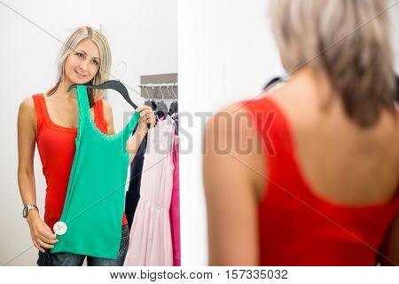 Young woman shopping in a fashion store, trying on some clothes she likes (color toned image; shallow DOF)
