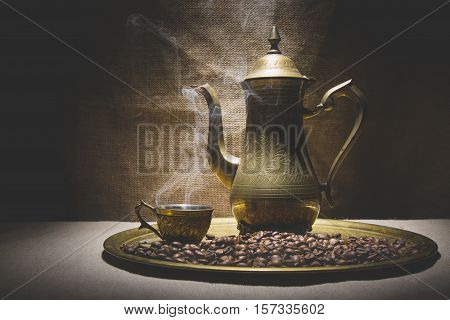 Vintage still life with heap of coffee beans near old copper coffeepot and cup with smoke on canvas background.